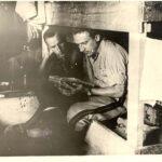 Compagni di prigionia di Rimero Chiodi ritratti mentre leggono all'interno della baracca
